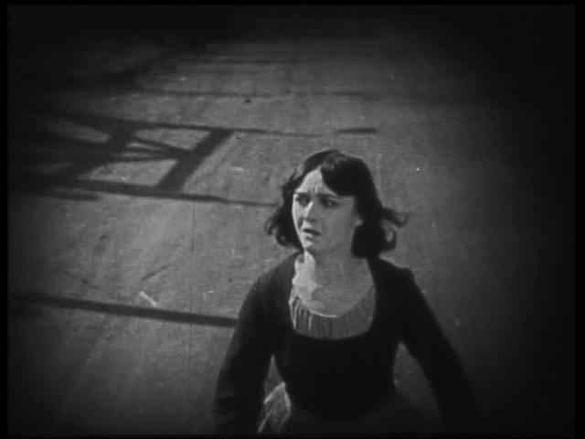 Mona tries to flee both the Germans and the French with the prison camp looming behind her.